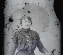 Staand portret van jonge vrouw in feestkledij bestaande uit lange rok en bloes met lange mouwen, stropdas en halsketting, bolvormig gekamd haar, Melle, 1910-1920
