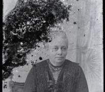 Zittende foto van vrouw in feestkledij bestaande uit rok en vestje met driekwartmouwen, strak naar achter gekamd haar, Melle, 1910-1920