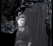Zittende foto van vrouw in feestkledij en golvend opgestoken haar, Melle, 1910-1920